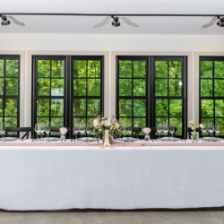 head table in front of tree lined windows at south haven creations venue