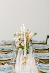 table setting with blue napkins at south haven creations wedding venue