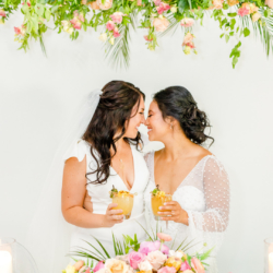 couple with hanging flowers by head table at south haven creations venue