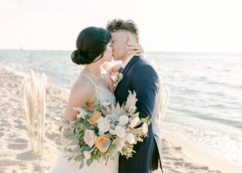 wedding couple on beach kissing
