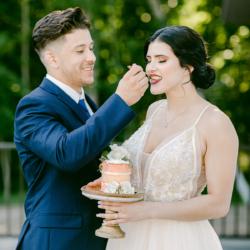 wedding couple eating cake on venue deck